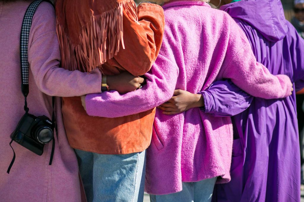 An image of four people dressed in shades of purple with arms around each other in community.